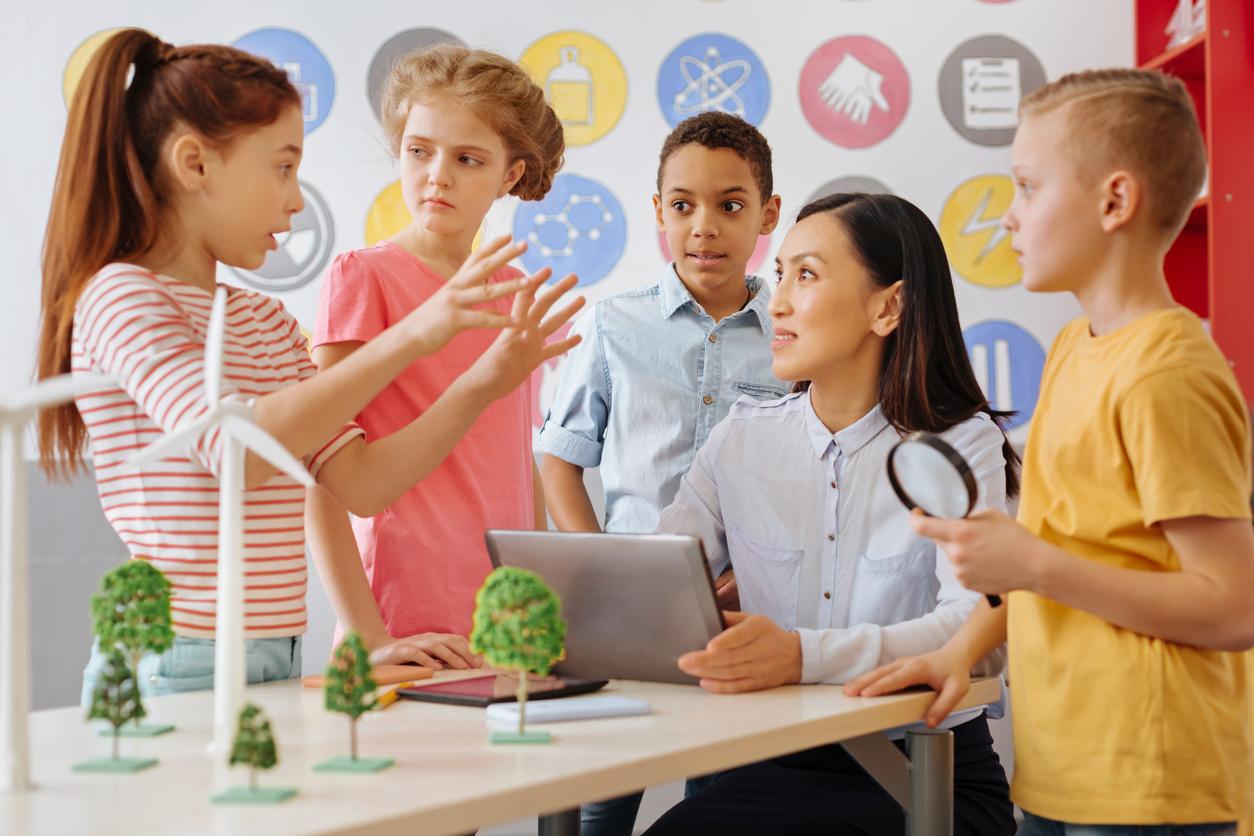 Smart schoolchildren sharing their ecology project idea with teacher