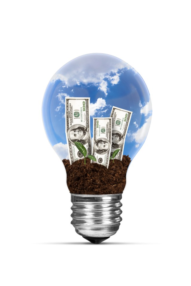 Light Bulb Growing Dollar Bills Reflecting Reduction In Utility Costs