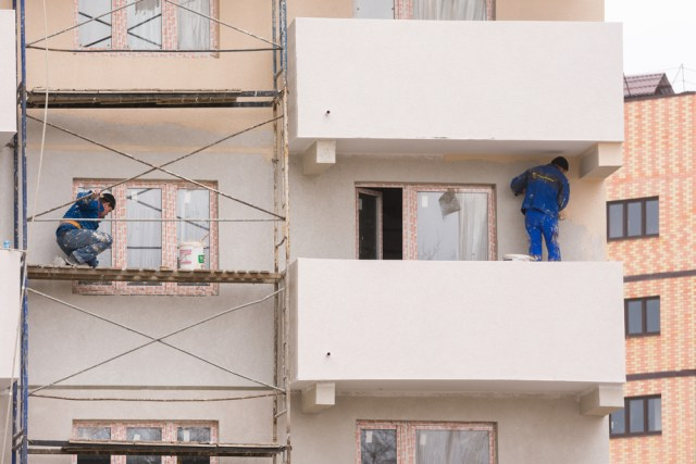 Two Painters Working On Exterior Repaint of Balconies And Walls At Apartment Building