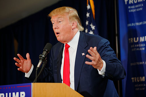 """Colored photograph of Donald Trump, wearing a navy suit, white shirt and red tie, speaking, with hands raised in an open  gesture."