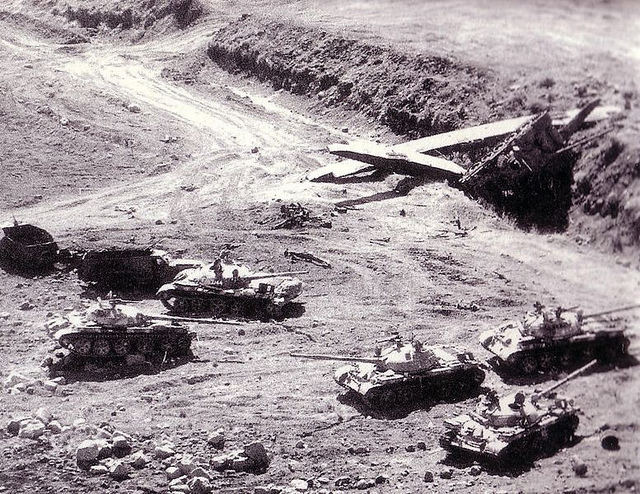 Black and white photograph showing 5 tanks on the battlefield and one on its side  in a ditch with a low-flying plane nearby. Syria to blame?