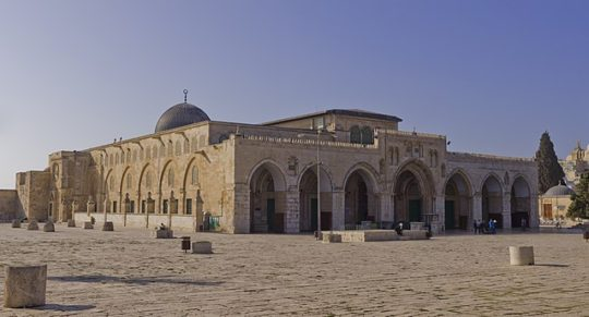 "Colored photograph of the Al-Aqsa Mosque on the Jewish Temple Mount. Stone building with arches and a dome. ""Burdensome stone"""
