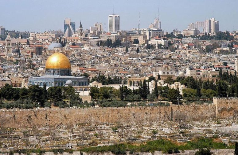 "Colored photograph of the city of Jerusalem, looking across the Temple Mount to the modern skyline. ""Burdensome stone""."