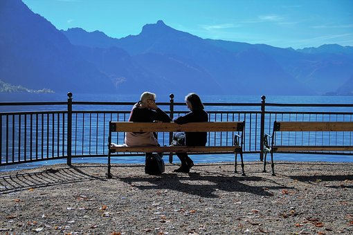 "Colored photograph of two women sitting on bench overlooking very blue-looking mountains. ""Burdensome stone"""