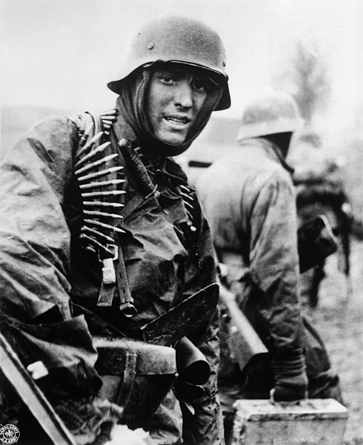 Black and white photograph of German SS soldier in winter uniform with a German helmet, a balaclava and a machine gun belt draped over his shoulder. Other soldier, with an ammunition case,  is in background. 200 million horsemen.                                                                 is in background . 200 million horsemen.