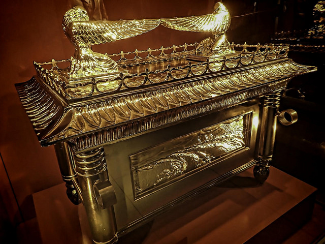 A colored photograph of a replica of the Jewish Ark of the Covenant. Gold with the two angels with their wings pointing to the center. Red background.