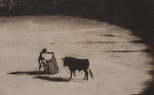 Black and white photograph of a matador holding a cape and bull approaching him. Large empty arena. Beast Interface.