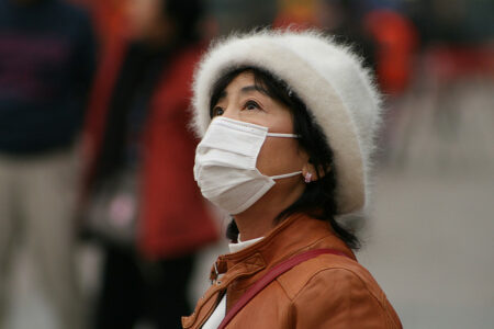 Colored photograph of Chinese lady wearing a soft woolly hat and russet jacket, looking up with face mask. Mark from the East.