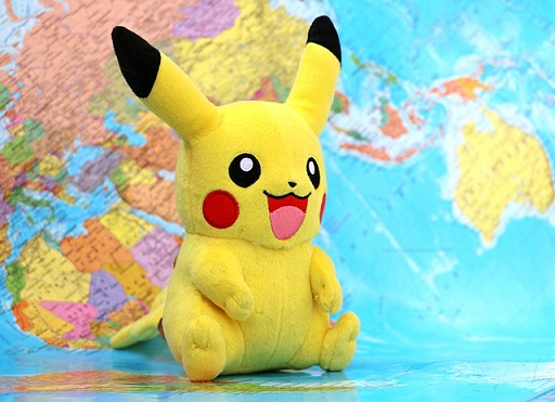 Colored photograph of  yellow Pokemon soft toy seated in front of a map of the world. Better than Pokemon.
