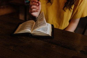 Colored photograph showing part of a girl's upper body in yellow T-shirt, with hand poised above open Bible. Bible is on dark brown table. Prophecy for Youth.