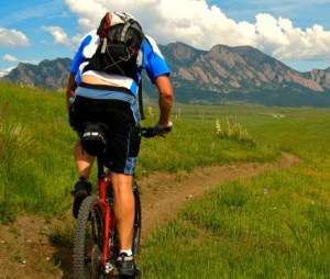 Man mountain biking towards Boulder Flatirons