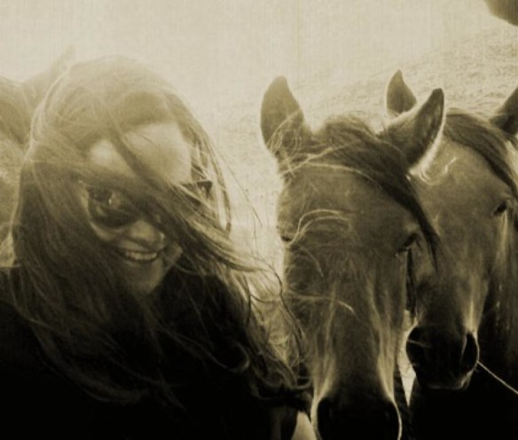 Anne Novak with friendly wild horses. (Photo © Irma Novak)