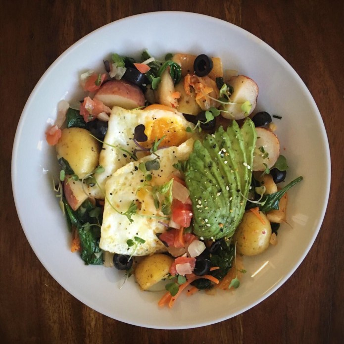 Two Fried Eggs, Potatoes, Avocado, Pico, Olives, Spinach, Carrots, and Microgreens