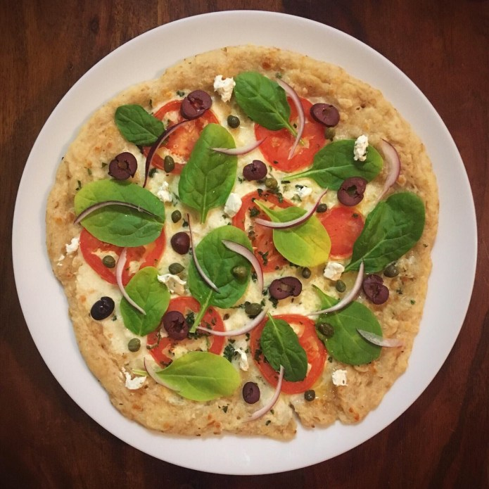Unbaked Pizza with Kalamata Olives, Spinach, tomatoes, Red Onions, Capers and Cheese