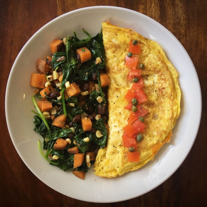 Leftover Butternut Squash, Pinto Beans, and Corn in a Spinach Salad with Cheese Omelette, topped with Tomatoes, and Capers