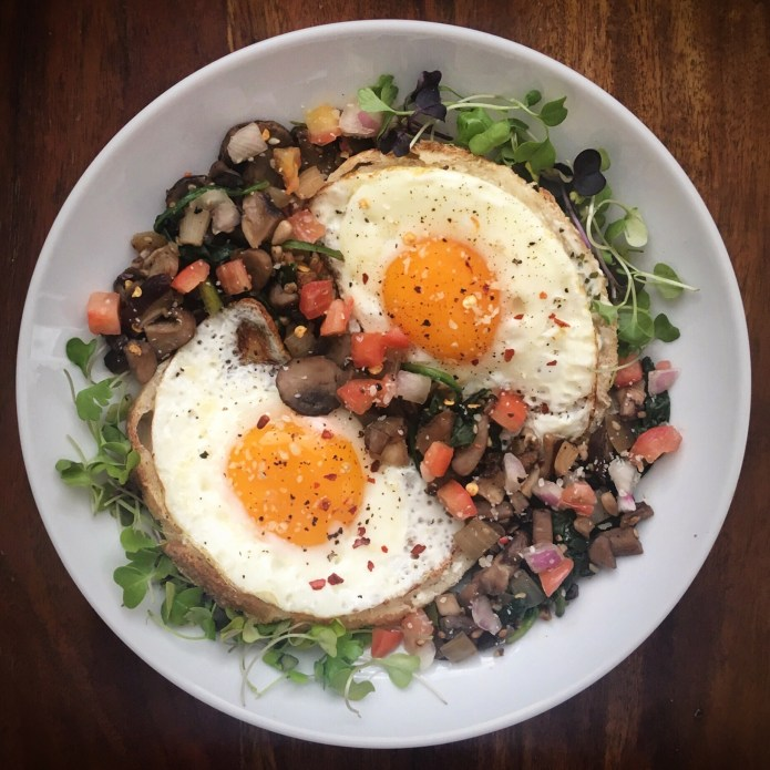 Food Nest with Eggs, Sunny Side Up, French Bread, Microgreens, and a Mushroom, Spinach, Tomato, Onion Sauté