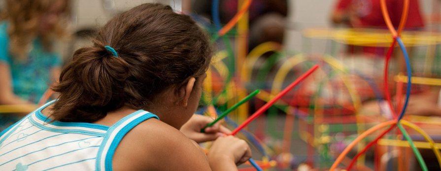 Dziecko bawiące się kolorowymi patyczkami