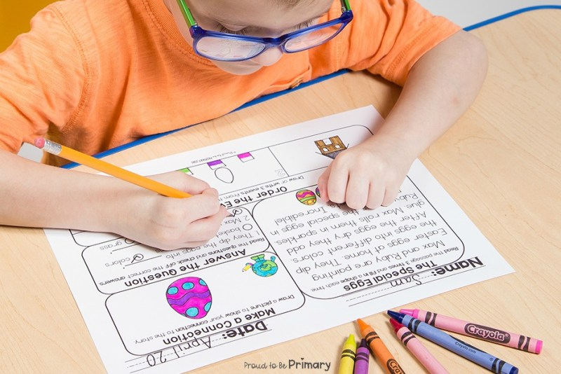 boy at table completing April spring comprehension mat activity with crayons