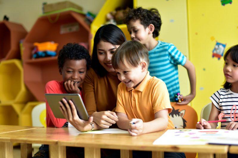 teacher teaching a small group on a tablet