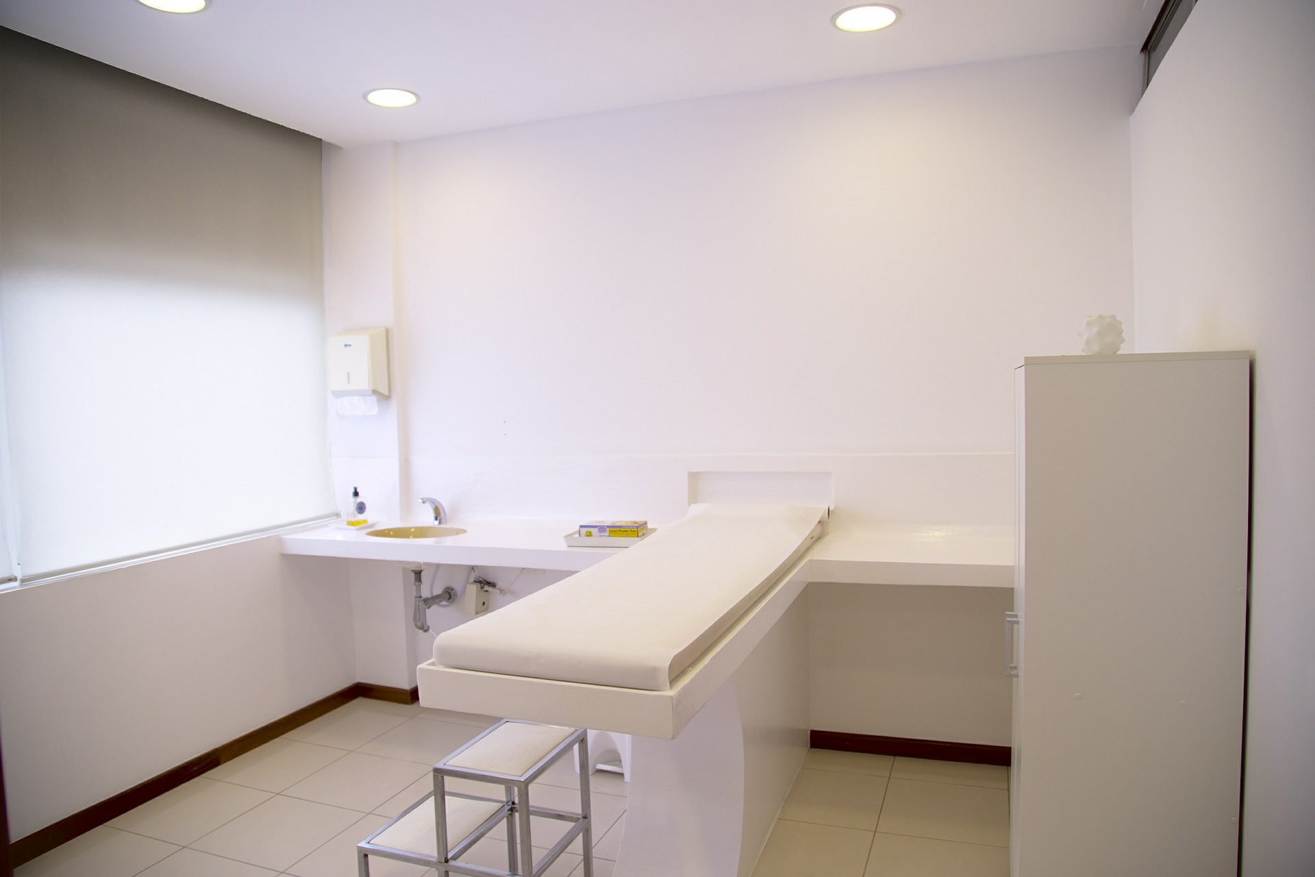 Minimalist medical treatment room with all white walls