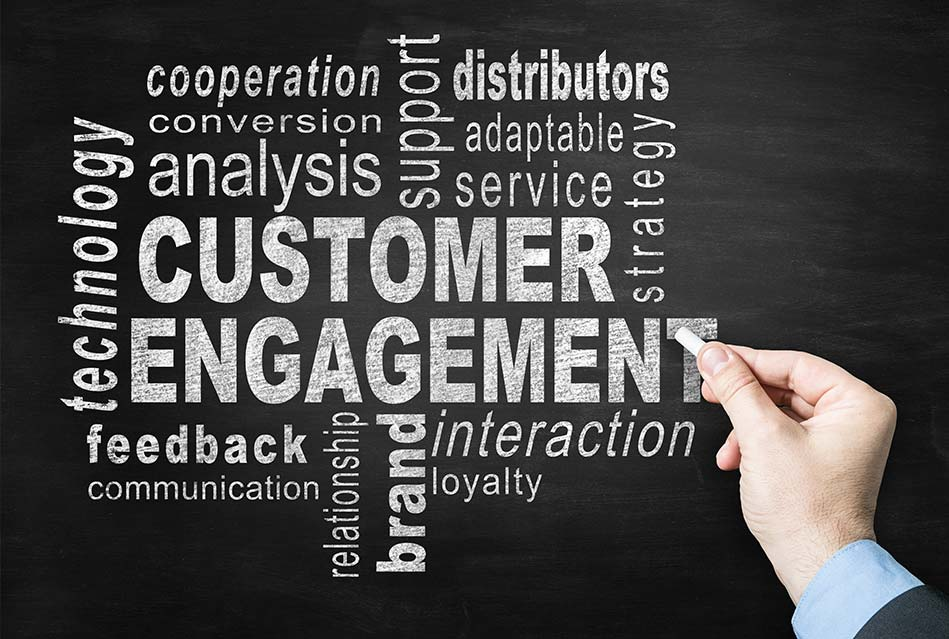 customer engagement and other terms written in white chalk on chalkboard; hand holding chalk doing final touches
