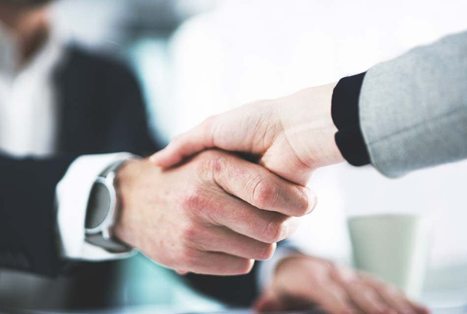 two property management service professionals shaking hands after after taking on a new client
