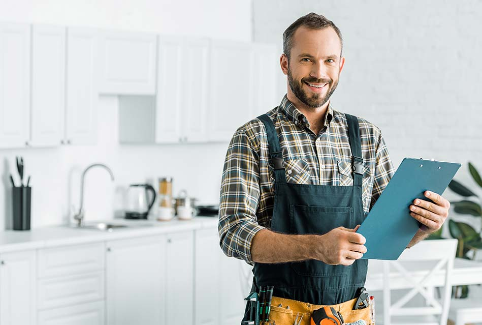 property contractor wearing green overalls, utility belt, holding checklist while standing in an all-white kitchen