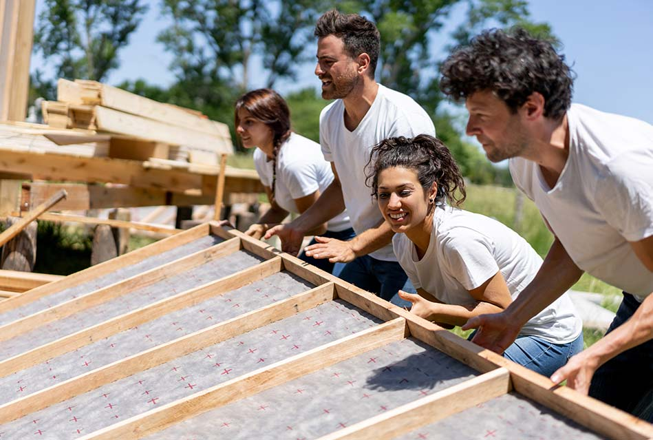 happy people in white t-shirts constructing the wall of a new home
