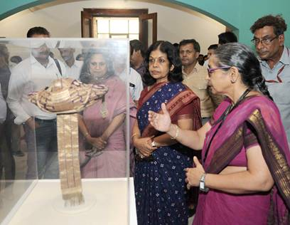 Rashmi Verma, Secretary, Ministry of Tourism and Ministry of Culture inspecting a traditional Indian head gear post inaugurating the exhibition