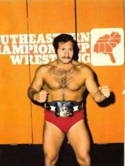 The Great Malenko wearing a wrestling belt posing with his fists up in front of the Southeastern Championship Wrestling Background