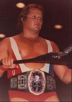 Bobby Roop in the ring wearing a USA sling and wrestling belt