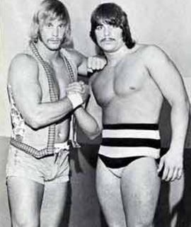 Wrestlers Randy Savage and Lanny Poffo joining hands to show unity and strength