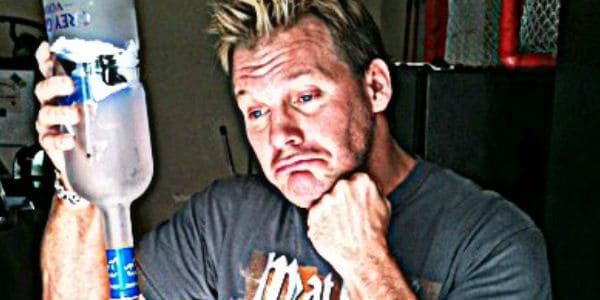 Chris Jericho frowning while holding an empty bottle of vodka upside down