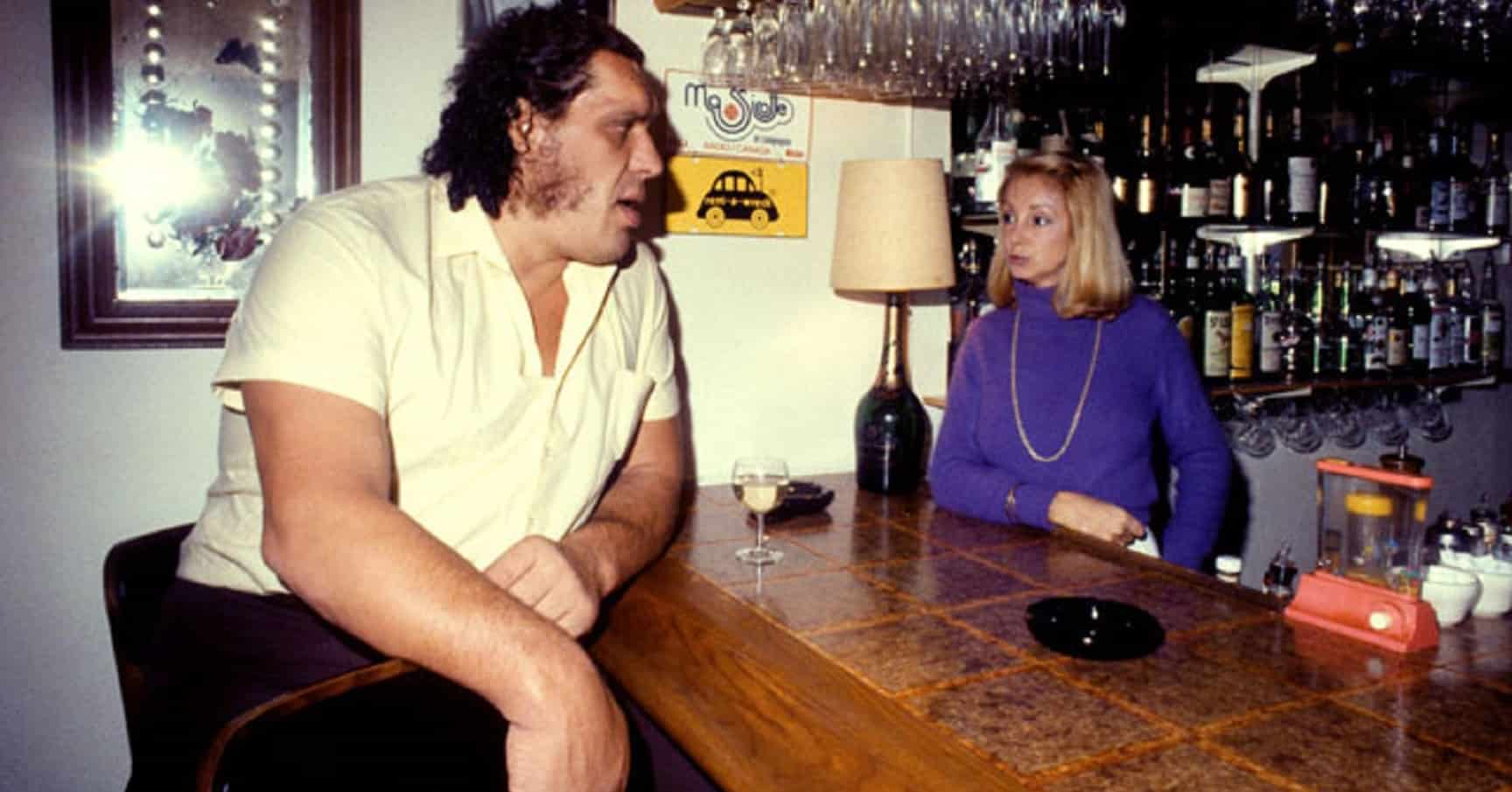 Andre the Giant sitting at a bar with a female bartender