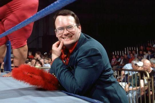 Him Cornette smiling as he stands at the side of the ring