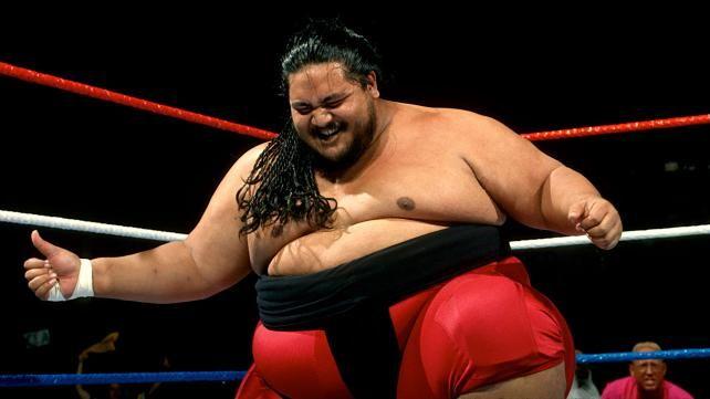 yokozuna on one knee smiling down in the ring