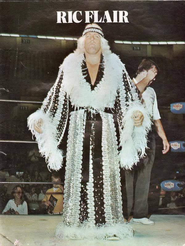 Ric Flair in a white silver and black zig zag sequin robe trimmed in white feathers and a matching headband in the ring
