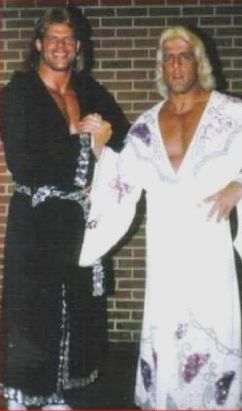 Lex Lugar and Ric Flair clasping hands both wearing sequin robes