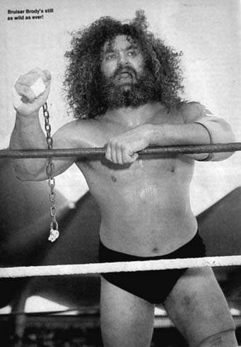 Bruiser Brody with wild hair leaning on the ring ropes holding a metal chain