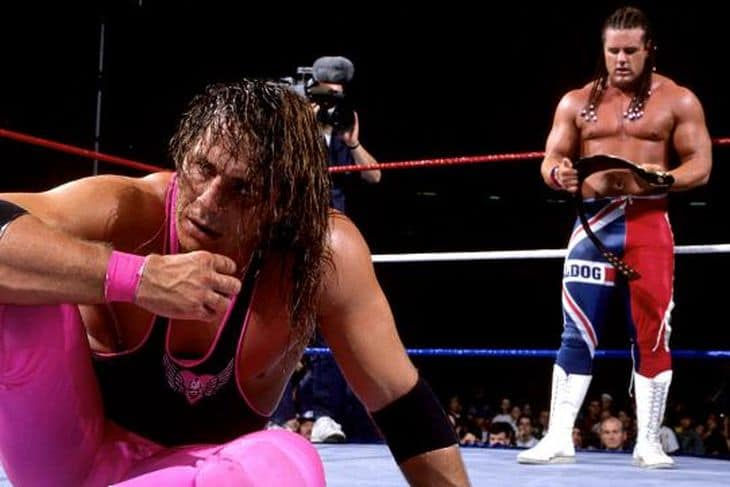 Bret Hart looking defeated as the British Bulldog holds the intercontinental title belt at the end of SummerSlam 1992