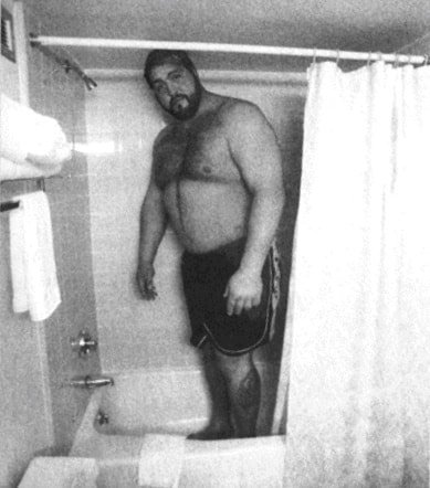 Big Show in a shower on the road having to bend his head which touches the ceiling
