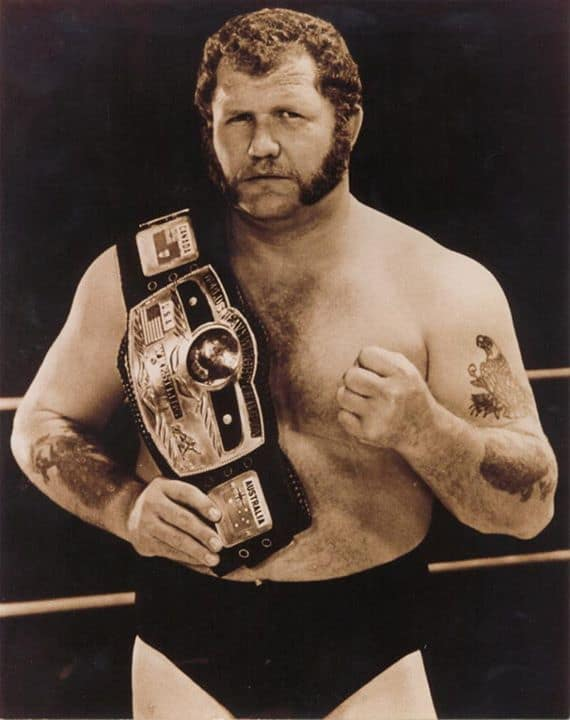 Harley Race posing in the ring with a title belt on this shoulder and his left hand in a fist