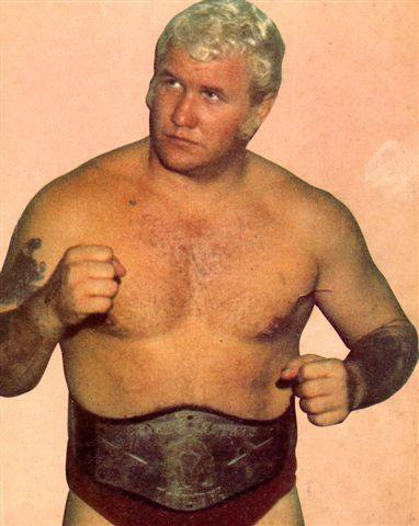 A younger harley Race posing with fists clenched as if ready to fight with his title belt on