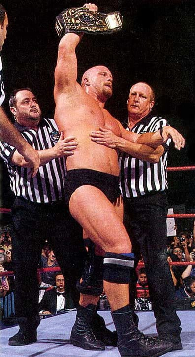 Stone Cold Steve Austin holding up the belt after his neck injury career ending match