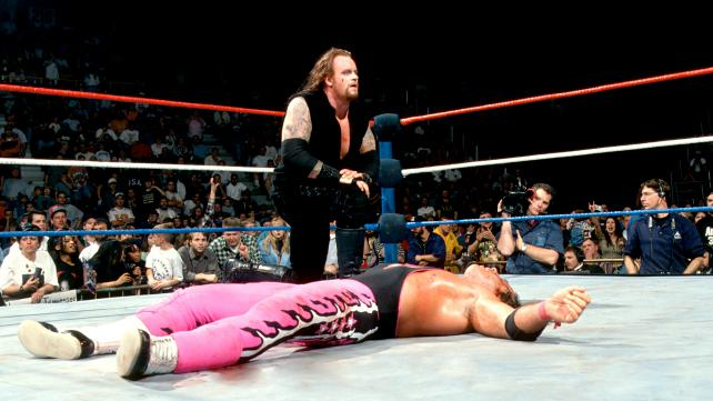 The Undertaker on one knee beside Bret Hart as he lay flat on his back