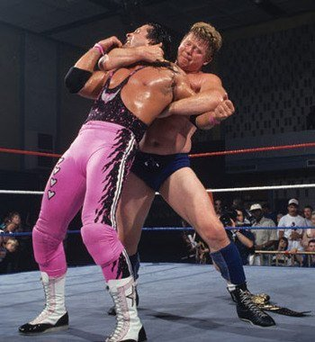 Bob Backlund with his arm around Bret's neck and his left arm locked during a match