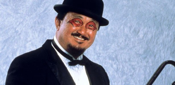 Mr. Fuji in his black bowler hat and a black tuxedo with red and black eye makeup on