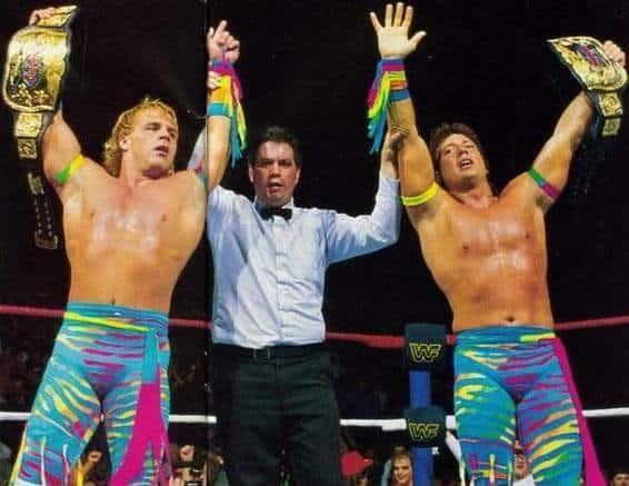 The Rockers (Shawn Michaels and Marty Jannetty) holding the title belts with the referee holding up their arms as winners the match