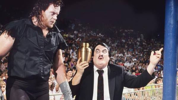 The Undertaker heading into the ring with Paul Bearer holding an urn