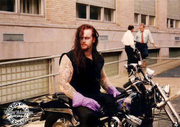 The undertaker backstage sitting on one of his motorcycles with purple gloves on.